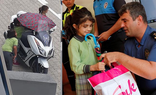Polis motosikletini yağmurdan koruyan öğrenciye ödül